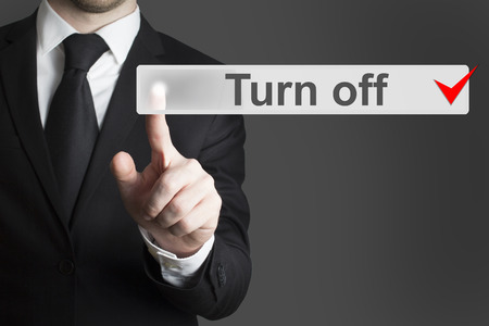 businessman in black suit pushing flat touchscreen button turn off photo