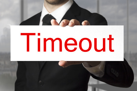 businessman in blach suit holding sign timeout photo