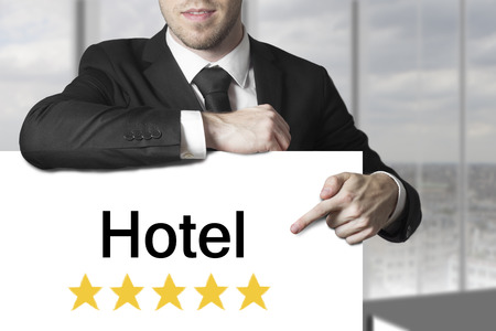 businessman in black suit pointing on sign hotel golden star rating photo