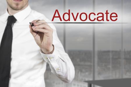 advocate: hombre de negocios en sala de oficina escribiendo defensor en el aire