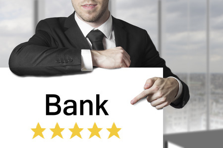 businessman in black suit pointing on sign bank golden star rating photo