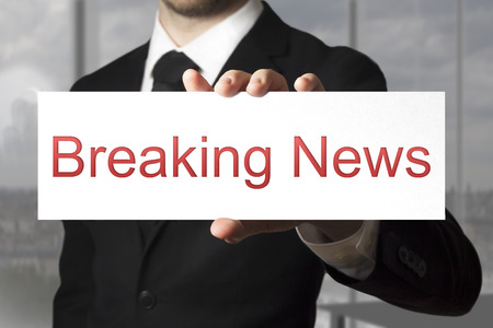 businessman in black suit showing sign breaking news photo