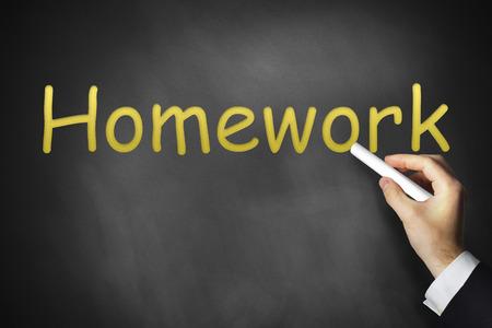 outwork: hand writing homework on black chalkboard