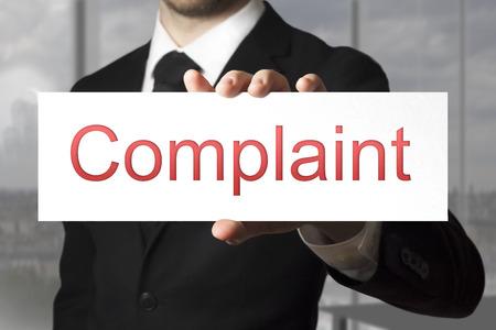 businessman in black suit showing sign complaint