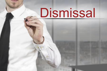 dismissal: businessman in office writing dismissal in the air