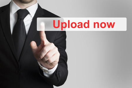 downloadable: businessman in black suit pushing flat touchscreen button upload now Stock Photo