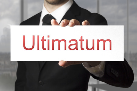 ultimatum: businessman in black suit holding sign ultimatum