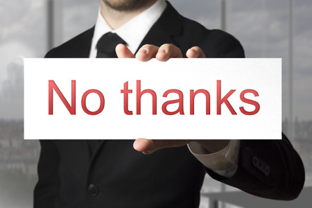 businessman in black suit holding sign no thanks refusal