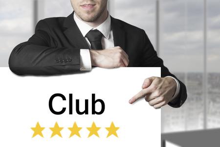 proved: uomo d'affari in abito nero che punta su bianco segno di club stelle dorate Archivio Fotografico