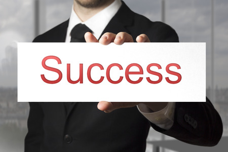 sign in: businessman in black suit showing sign success career