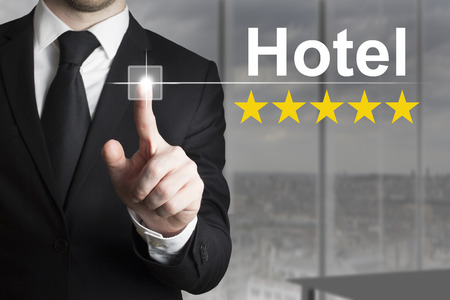 five star: businessman in black suit pushing button hotel five star rating