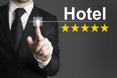proved: uomo d'affari in abito nero spingendo albergo pulsante stella dorata voto Archivio Fotografico