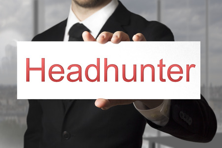 headhunter: businessman in black suit holding white sign headhunter