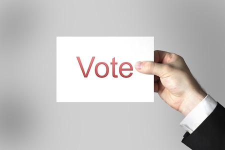 conservative: businessmans hand holding card vote