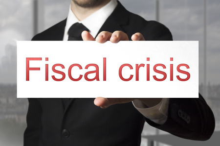 failed politics: businessman in black suit holding sign fiscal crisis Stock Photo