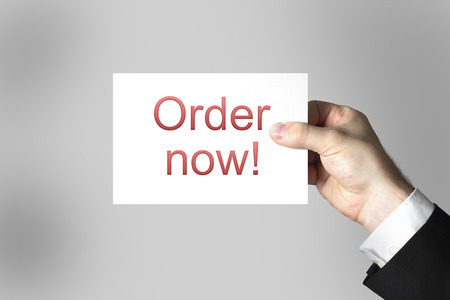 preorder: businessmans hand holding card sign order now Stock Photo