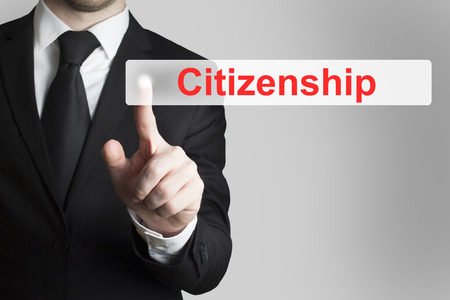 citizenship: businessman in black suit pushing flat button citizenship Stock Photo