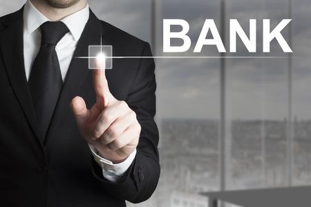 international crisis: businessman in black suit pushing button bank Stock Photo