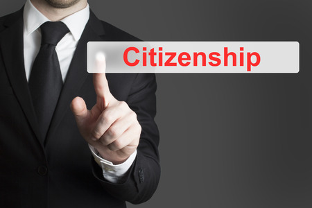 citizenship: businessman in black suit pushing flat touchscreen button citizenship