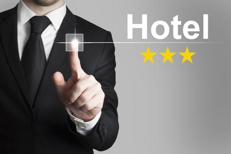proved: uomo d'affari in abito nero che spinge il tasto albergo a tre stelle