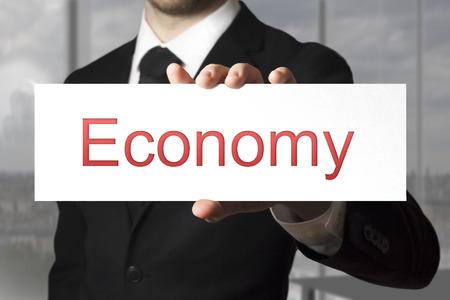 failed politics: businessman in black suit showing sign economy