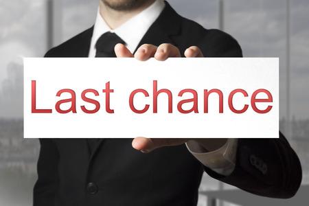 decission: businessman in black suit holding sign last chance