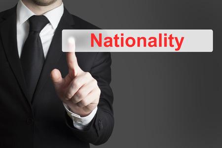 pushing the button: hombre de negocios en traje negro pulsando el bot�n de la nacionalidad