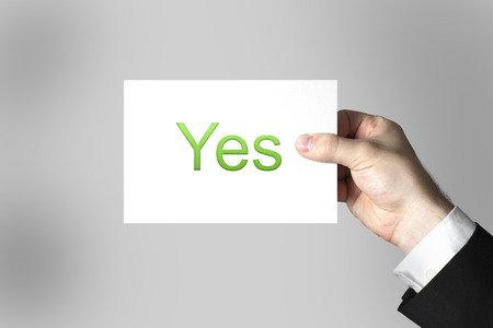 approbation: hand holding small white sign yes green Stock Photo