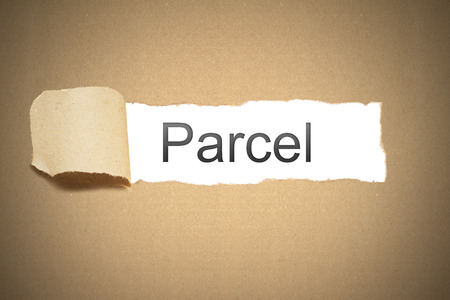 brown packaging paper torn to reveal parcel photo