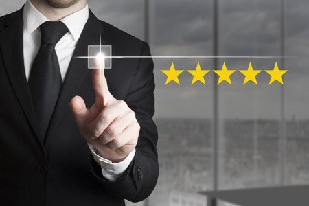 hotel reviews: businessman in black suit pushing button five star rating