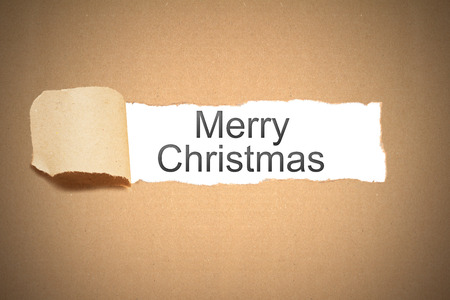 reveal: brown packaging paper torn to reveal merry christmas Stock Photo