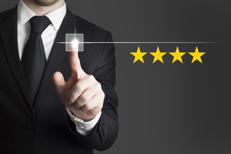 businessman in black suit pushing button four star rating photo
