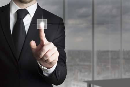 businessman in black suit pushing small touchscreen button photo