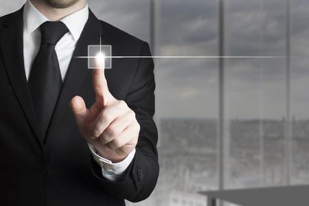 businessman in black suit pushing small touchscreen button Standard-Bild