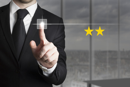 businessman in black suit pushing button two star rating photo