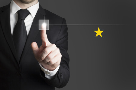 pushing button: businessman in black suit pushing button single gold star Stock Photo