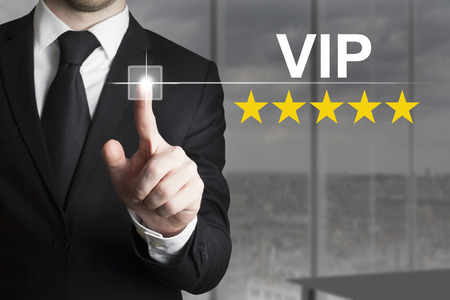 vip: businessman in black suit pushing button vip five gold stars