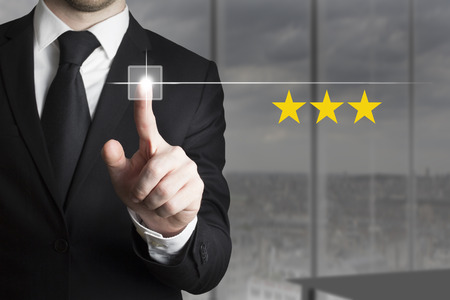 restaurant rating: businessman in black suit pushing button three stars rating