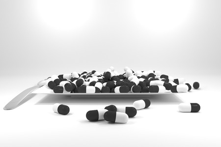 starvation: large pile of black colored pills on white plate Stock Photo