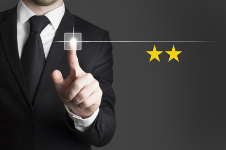 businessman in black suit pushing touchscreen button two rating stars photo