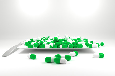 starvation: large pile of green colored pills on white plate silver spoon