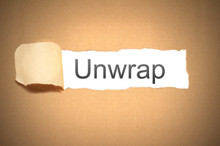 reveal: old brown package paper carton torn to reveal white space unwrap