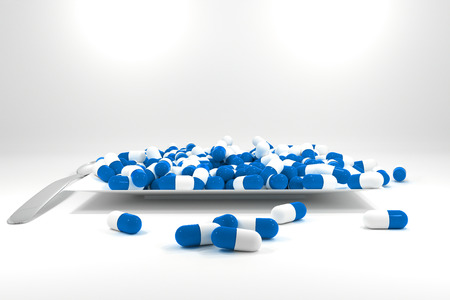 large pile of blue colored pills on white plate silver spoon photo
