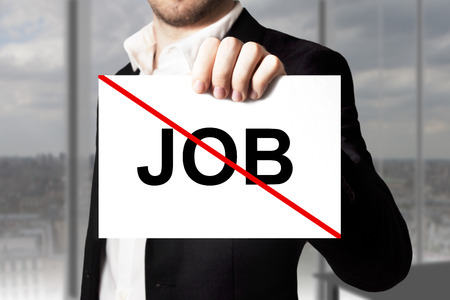 decission: businessman in black suit holding sign job crossed out jobless
