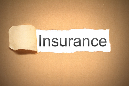 reveal: brown packaging paper torn to reveal insurance Stock Photo