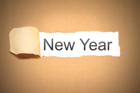 reveal: brown packaging paper torn to reveal new year Stock Photo