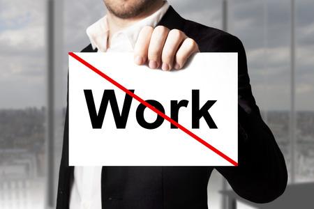decission: uomo d'affari in vestito nero che tiene segno lavoro barrato Archivio Fotografico