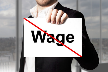 poorly: businessman in black suit holding sign wage crossed out