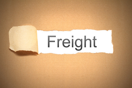 reveal: brown packaging paper torn to reveal freight Stock Photo