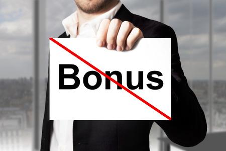cutback: businessman in black suit holding sign bonus crossed out